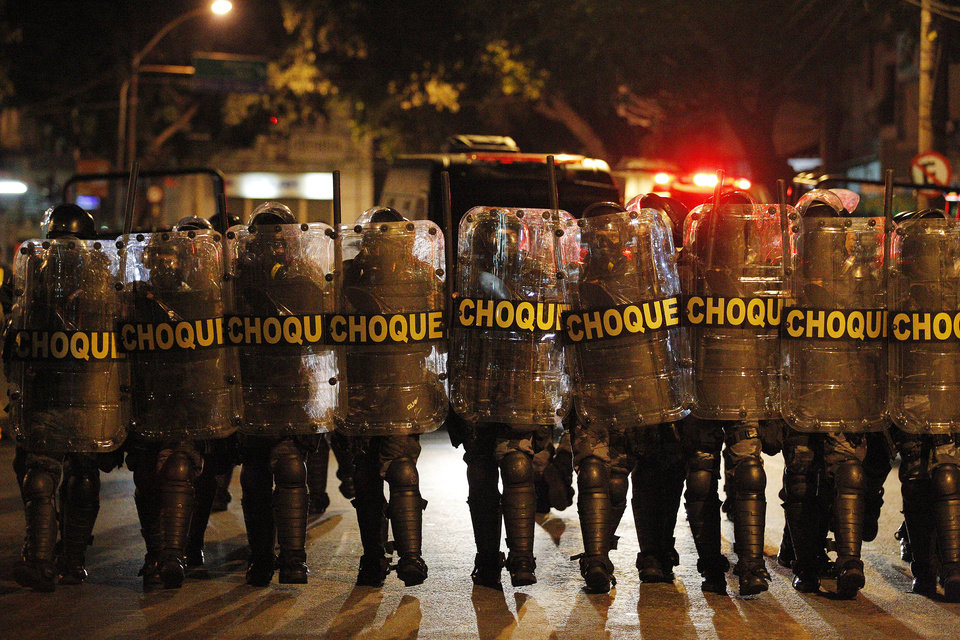 Photo - Police advance on anti-World Cup demonstrators demanding better public services and protesting the money spent on the World Cup soccer tournament near Maracana stadium in Rio de Janeiro, Brazil, Sunday, June 15, 2014. Police clashed with protesters marching toward the stadium ahead of the match between Argentina and Bosnia. (AP Photo/Leo Correa)