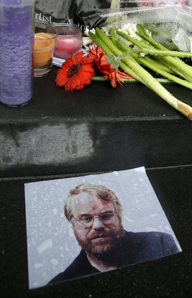 Photo - A makeshift memorial is seen, Monday, Feb. 3, 2014, outside the building where the body of actor Philip Seymour Hoffman was found in New York. Hoffman, 46, was found dead Sunday in his apartment. (AP Photo/Seth Wenig)