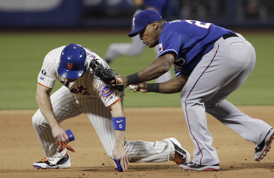 Photo - New York Mets' David Wright, left, is caught between second and third base in a rundown by Texas Rangers third baseman Adrian Beltre in the fifth inning of a baseball game at Citi Field, Saturday, July 5, 2014, in New York. (AP Photo/Mark Lennihan)