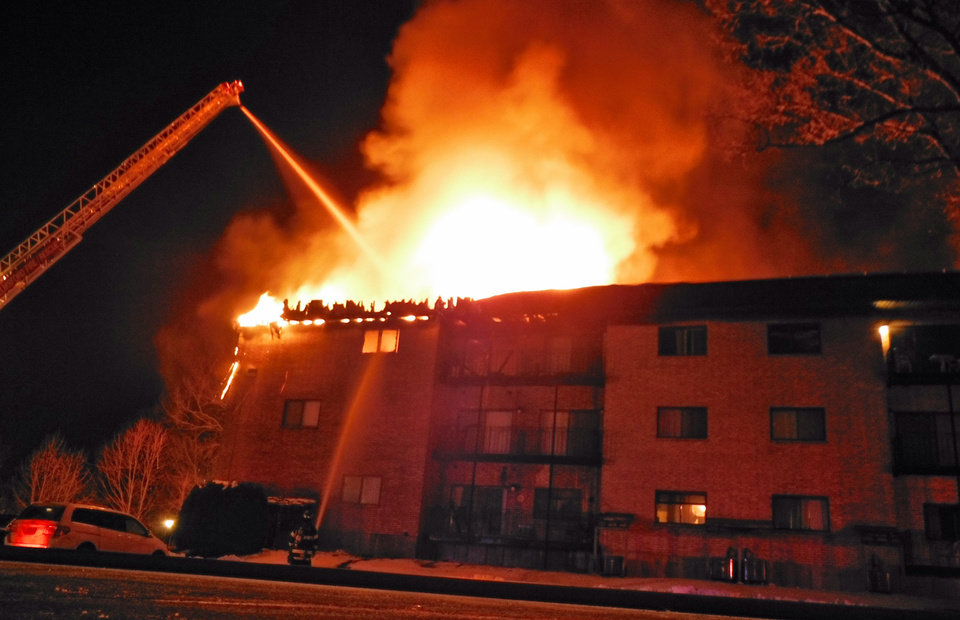 Firefighters form Lowell\'s Ladder #3 fight a condominium fire Saturday Jan. 5, 2013 in Chelmsford, Mass. The state fire marshal says two people died and four others were injured in the fire in northeastern Massachusetts. (AP Photo/The Lowell Sun, Robert Mills)