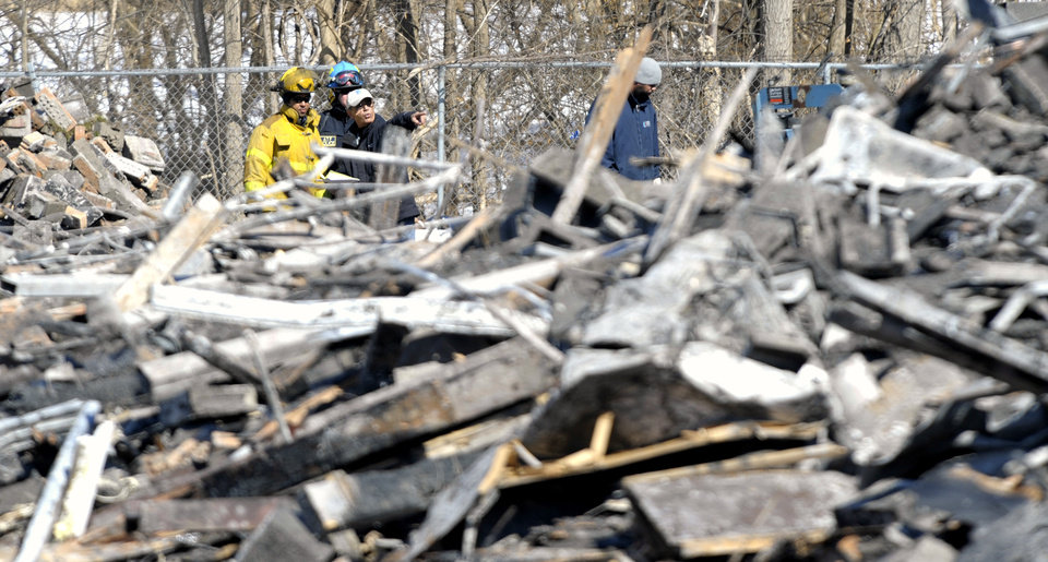 Photo - Officials from the ATF and Detroit Fire Department survey the debris from a 4-alarm fire at the Jason Manor Apartments on Jason at Schoolcraft on the Northside of Detroit, Thursday, March 6, 2014. Firefighters battled the blaze early Wednesday morning and now officials have confirmed, the fire that left dozens of residents homeless, was caused by arson. (AP Photo/ The Detroit News, Todd McInturf)