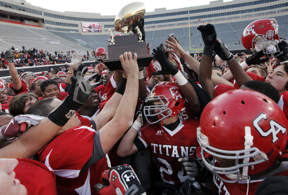 The Carl Albert Titans celebrate with the championship trophy after the Class 5A state high school football championship game between Bixby and Carl Albert at Boone Pickens Stadium in Stillwater, Okla., Saturday, December 5, 2009. Carl Albert won, 21-7.  Photo by Nate Billings, The Oklahoman