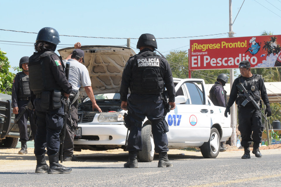 Photo - State police check a taxi at a roadblock due to stepped up security after masked armed men broke into a beach home, raping six Spanish tourists who had rented the house in Acapulco, Mexico, Tuesday Feb. 5, 2013. According to the mayor of Acapulco, five masked men burst into a house the Spaniards had rented on the outskirts of Acapulco, in a low-key area near the beach, and held a group of six Spanish men and one Mexican woman at gunpoint, while they raped the Spanish women before dawn on Monday. (AP Photo/Bernandino Hernandez)