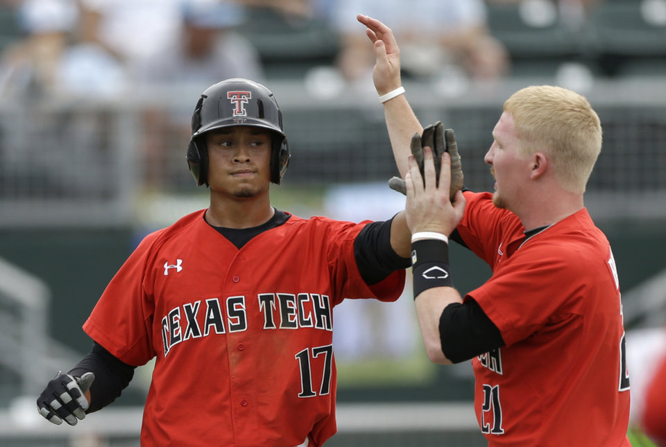 Photo - Texas Tech's Zach Davis (17) is congratulated byBryant Burleson (21) after Davis scored the game-winning run on a double by Eric Gutierrez against Columbia during the ninth inning of an NCAA college baseball regional tournament game in Coral Gables, Fla., Friday, May 30, 2014. Texas Tech won 3-2. (AP Photo/Alan Diaz)