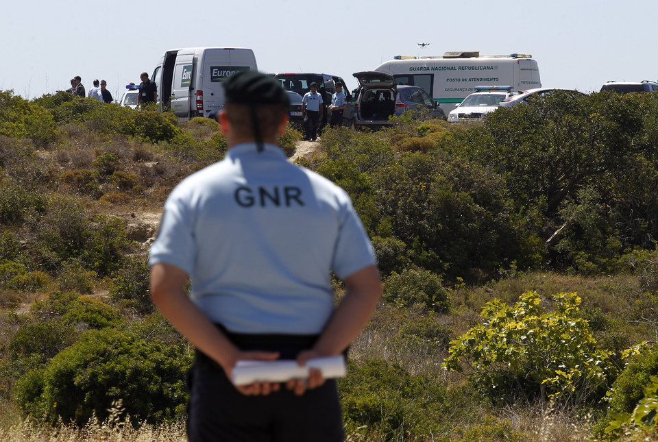 Photo - Portuguese Republican Guard policemen and other officers stand guard in a cordoned-off area, in Praia da Luz, Lagos, southern Portugal, Monday, June 2, 2014. Police investigating the disappearance of Madeleine McCann cordoned off Monday an area of scrubland near where the British girl vanished seven years ago. Officers placed yellow-and-white police tape around the waste ground, which is mostly level and slightly larger than a soccer field, and were expected to conduct a forensic examination of the area in the coming days. (AP Photo/Francisco Seco)