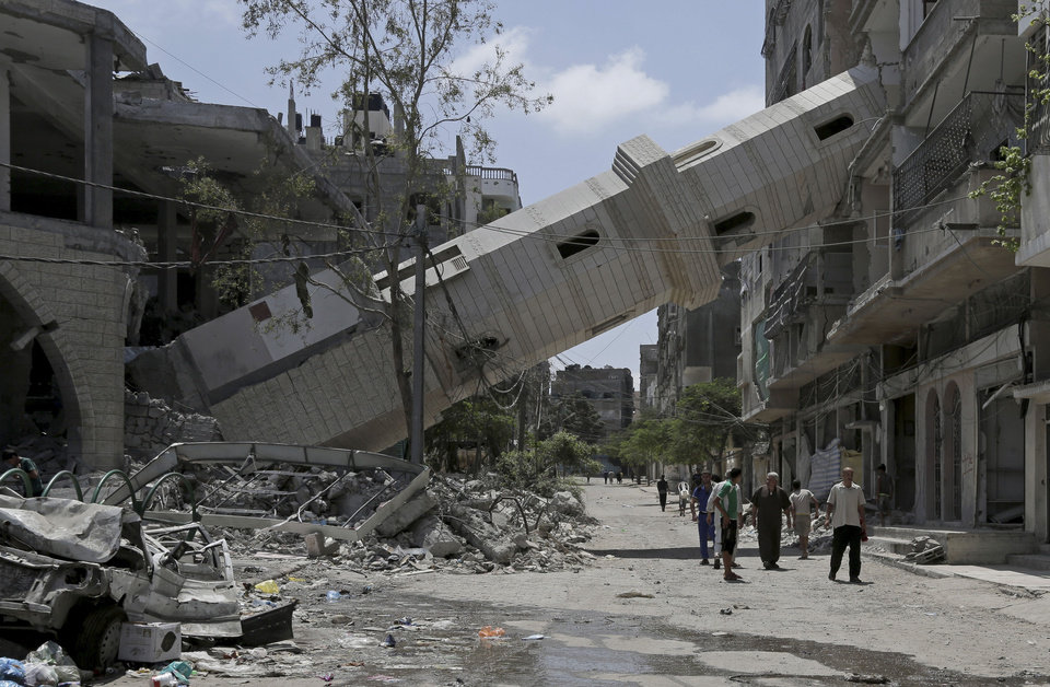 Photo - Palestinians walk under the fallen minaret of the Al-Sousi mosque that was destroyed in an Israeli strike at Shati refugee camp in Gaza City in the northern Gaza Strip on Friday, Aug. 22, 2014. (AP Photo/Adel Hana)