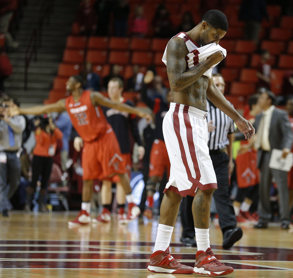 Photo - Oklahoma's Cameron Clark (21) walks off the court as Texas Tech celebrates after an NCAA college basketball game between the University of Oklahoma and Texas Tech University at the Lloyd Noble Center in Norman, Okla., Wednesday, Feb. 12, 2014. Oklahoma lost 68-60. Photo by Bryan Terry, The Oklahoman