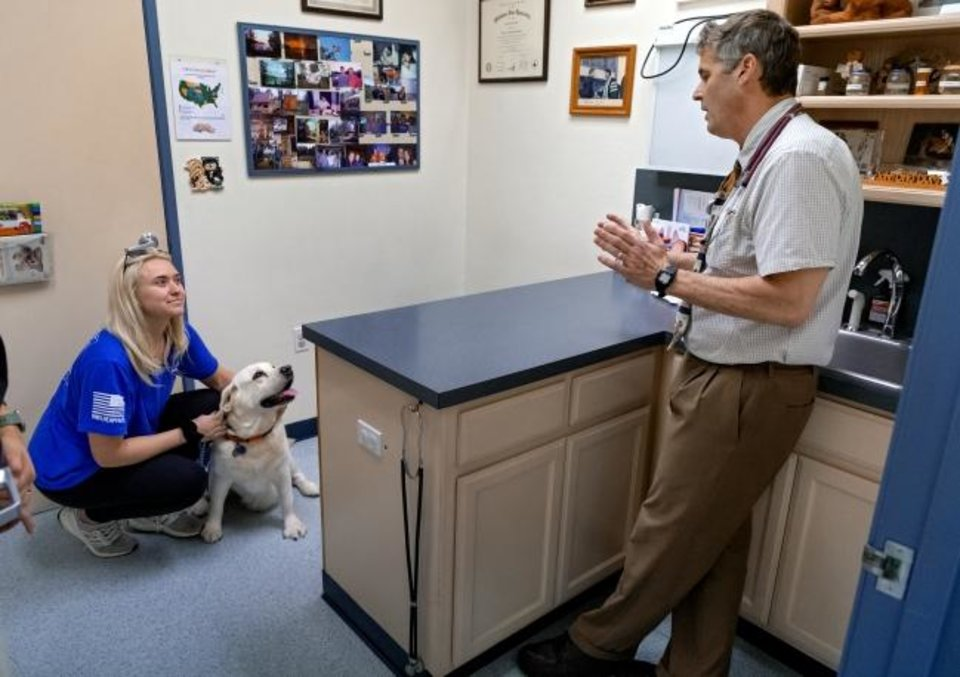 Photo -  Veterinary Dr. John Otto talks recently with Sam Sommer about her Brew at his University Animal Hospital office in Norman. [Chris Landsberger/The Oklahoman]
