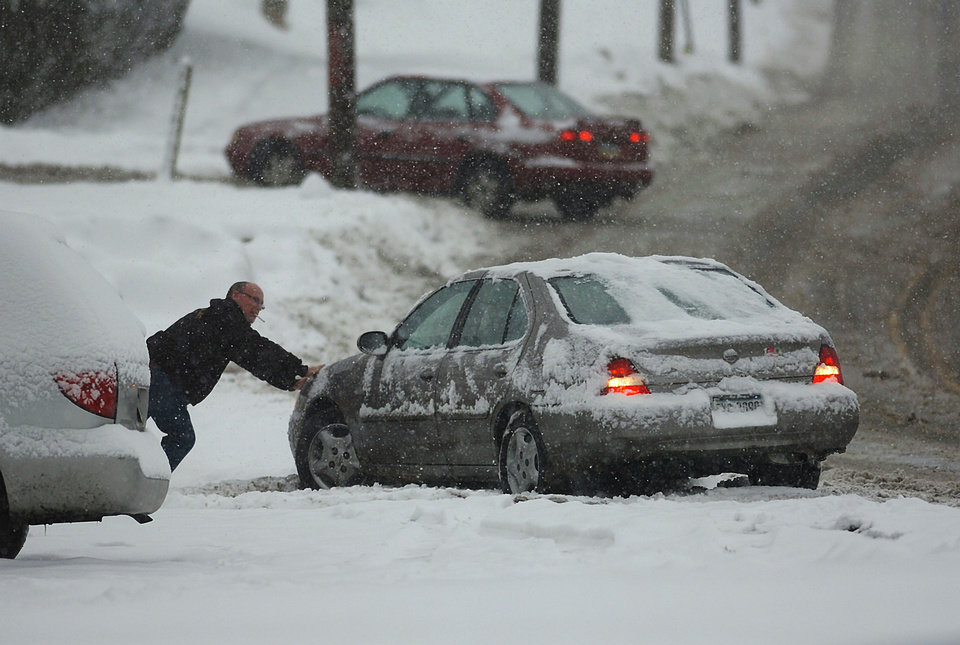 A resident helps out a motorist push his car out of the snow on an icy West Lackawanna Avenue in Blakely,  Pa. on Saturday, Dec. 29, 2012. Photo by Butch Comegys, The Scranton Times-Tribune/AP <strong>Butch Comegys</strong>