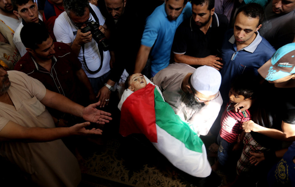Photo - Palestinian mourners gather around the lifeless body of one year-old Rizk Hayek, who was killed Friday by an Israeli tank shell, during his funeral in Gaza City, Saturday, July 19, 2014. Relatives say Rizk, was killed by shrapnel. (AP Photo/Hatem Moussa)
