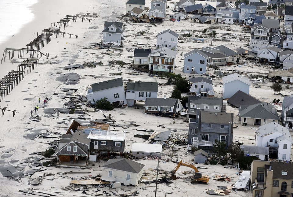 Photo - FILE - This Oct. 31, 2012 aerial file photo shows destruction in the wake of Superstorm Sandy in Seaside Heights, N.J.  Global warming is rapidly turning America into a stormy and dangerous place, with rising seas and disasters upending lives from flood-stricken Florida to the wildfire-ravaged West, according to a new U.S. federal scientific report released Tuesday, May 6, 2014. (AP Photo/Mike Groll, File)