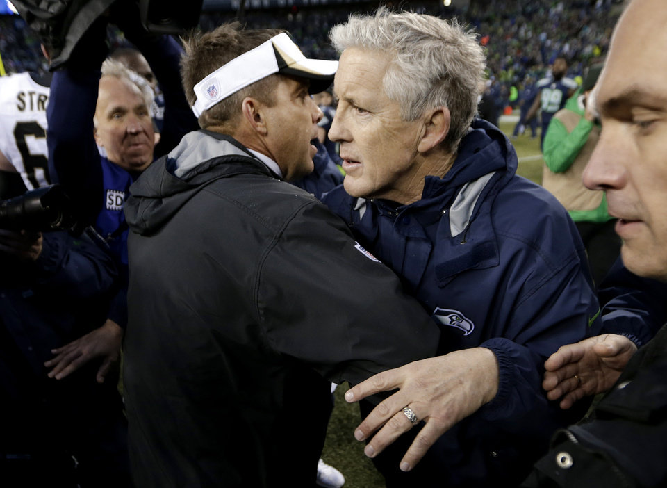 Photo - New Orleans Saints coach Sean Payton, left, hugs Seattle Seahawks coach Pete Carroll after an NFC divisional playoff NFL football game in Seattle, Saturday, Jan. 11, 2014. The Seahawks won 23-15. (AP Photo/John Froschauer)
