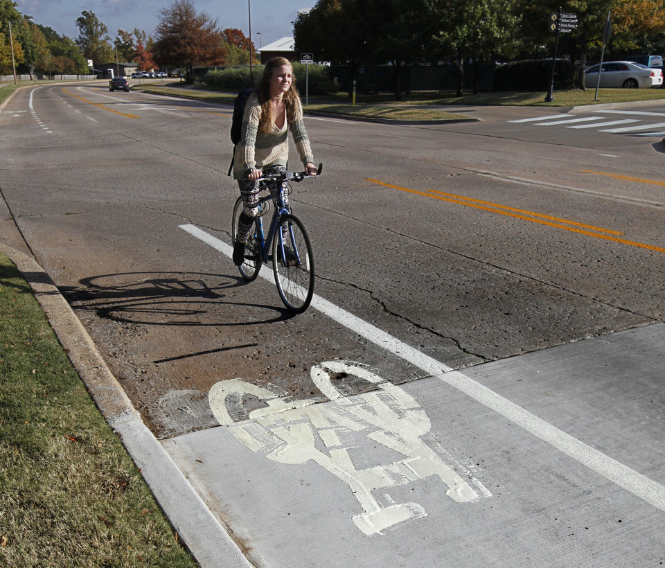 Photo - University of Central Oklahoma student Molly Reaves heads to class on Edmond's first bike lane along University Drive, which opened on Sunday. PHOTO BY PAUL HELLSTERN, THE OKLAHOMAN.  PAUL HELLSTERN - OKLAHOMAN