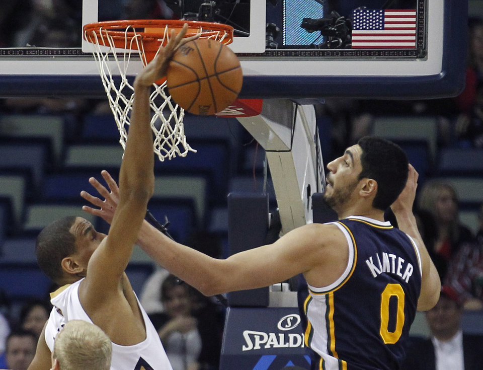 Photo - New Orleans Pelicans center Alexis Ajinca (42) battles Utah Jazz center Enes Kanter (0) for a rebound in the first half of an NBA basketball game in New Orleans, Friday, March 28, 2014. (AP Photo/Bill Haber)