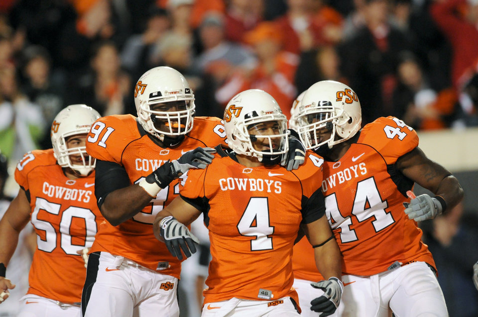 Oklahoma  State linebacker Patrick Lavine (4), is congratulated after scoring on an interception, by teammates Jamie Blatnick (50), Ugo Chinasa (91), and Donald Booker (44), during the second half of an NCAA college football game in Stillwater, Okla. Saturday, Nov. 14, 2009. AP Photo