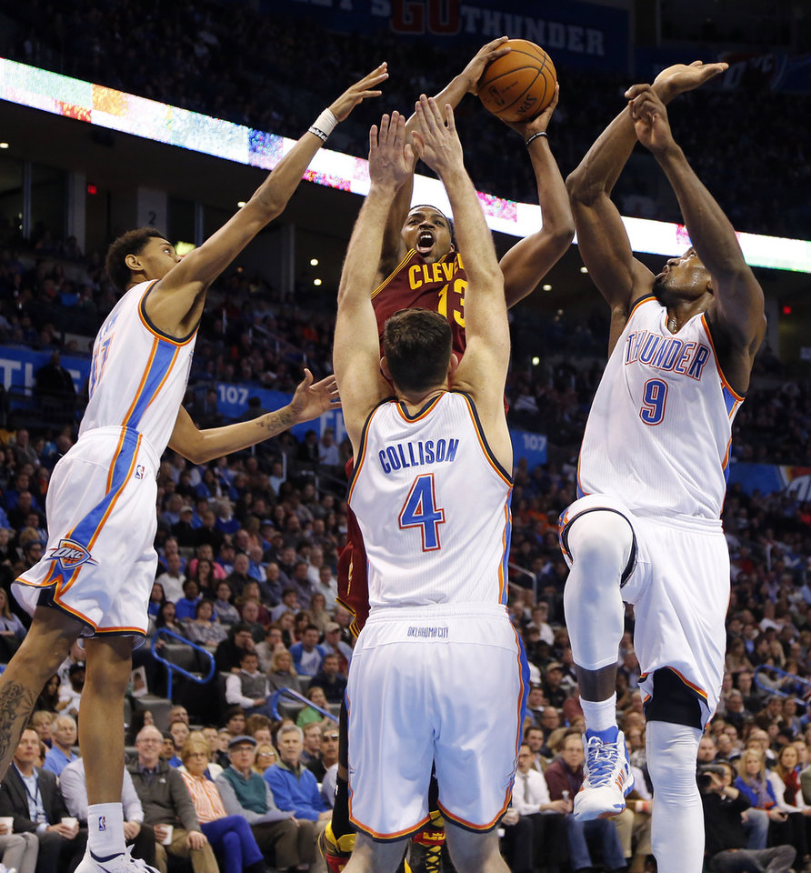 Photo - Oklahoma City's Jeremy Lamb (11), Nick Collison (4) and Serge Ibaka (9) try to stop Cleveland's Tristan Thompson (13) during the NBA basketball game between the Oklahoma City Thunder and the Cleveland Cavaliers at the Chesapeake Energy Arena in Oklahoma City, Okla. on Wednesday, Feb. 26, 2014.  Photo by Chris Landsberger, The Oklahoman