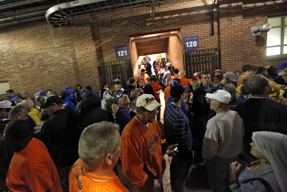 Photo - Football fans take cover in the concourse of the stadium as a storm delays the start of the college football game between Oklahoma State and Tulsa on Saturday in Tulsa. Photo by Chris Landsberger, The Oklahoman