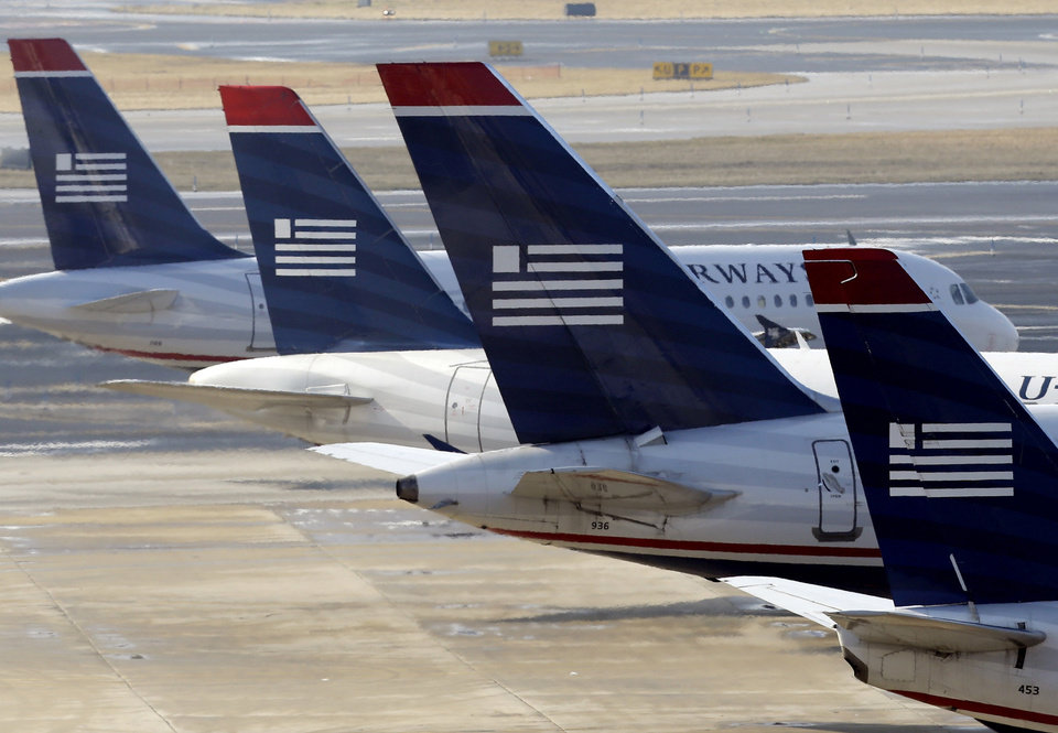 Photo - US Airways jets prepare for flight at their gates at the Philadelphia International Airport, Thursday, Feb. 14, 2013, in Philadelphia. The merger of US Airways and American Airlines has given birth to a mega airline with more passengers than any other in the world. (AP Photo/Matt Rourke)