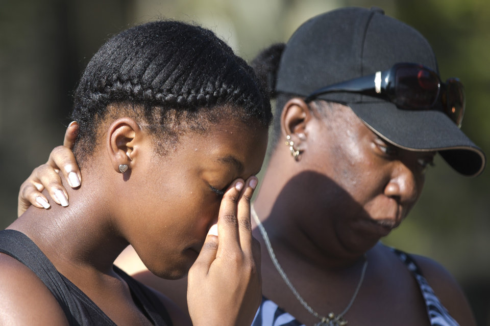 Photo - Riconya Jackson, left, and her mother Tonia Jackson pay their respects Monday, July 28, 2014, at a makeshift memorial for three children who were killed Friday by a hijacked car that lost control and hit a group of people, in Philadelphia. Police investigators are talking to two people in connection with the search for two carjackers who rammed a stolen sport utility vehicle into a family in north Philadelphia, killing three children. (AP Photo/Matt Rourke)