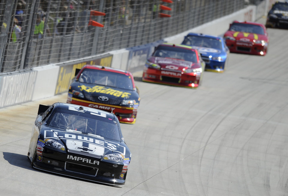 Jimmie Johnson, front, races his car against, from left to right, Clint Bowyer, Jeff Gordon, Brad Keselowski and Jamie McMurray during a NASCAR Sprint Cup Series auto race, Sunday, Sept. 30, 2012, at Dover International Speedway in Dover, Del. (AP Photo/Nick Wass)