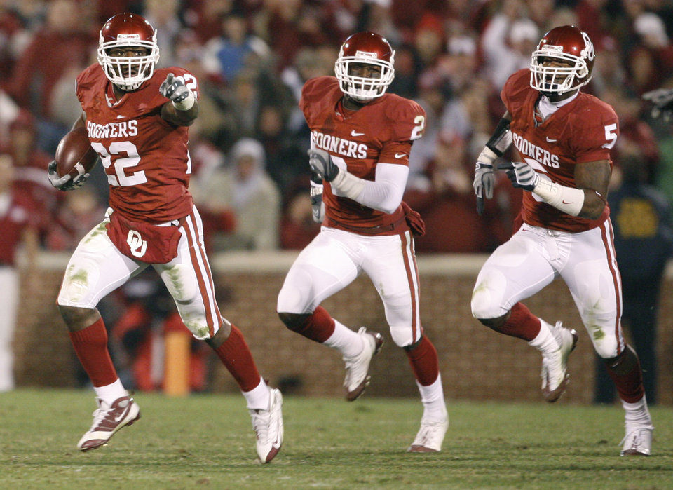 Photo - OU's Keenan Clayton, left, runs back a fumble followed by Brian Jackson, and Nic Harris during the college football game between the University of Oklahoma Sooners and Texas Tech University at Gaylord Family -- Oklahoma Memorial Stadium in Norman, Okla., Saturday, Nov. 22, 2008. BY BRYAN TERRY, THE OKLAHOMAN