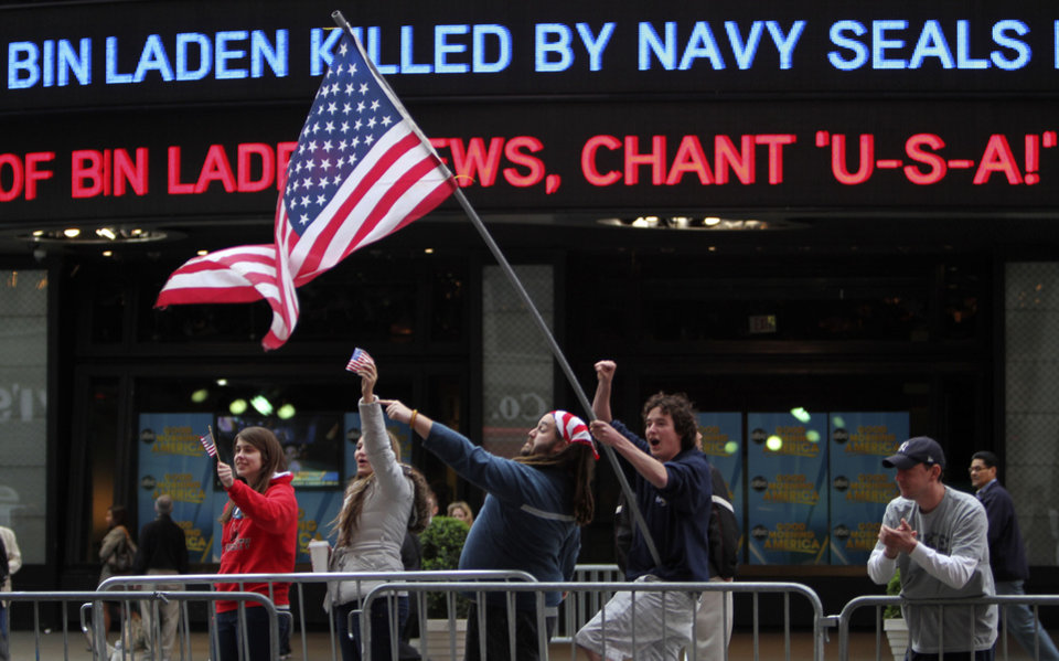 Photo - Melissa LaCour, left, Brittany McGarry, second from left, Bryan Murray, second from right, and Dennis Vincent celebrate outside the ABC studio in New York's Times Square as news of Osama bin Laden's death is announced on the ticker,  Monday, May 2, 2011.  (AP Photo/Mary Altaffer)