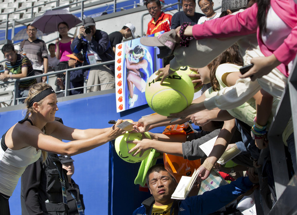 Photo -   Belarus' Victoria Azarenka, left, signs an autograph for spectators after defeating Romina Oprandi of Switzerland 6-2, 6-0 in their women's singles quarterfinal match of the China Open tennis tournament in Beijing Friday, Oct. 5, 2012. (AP Photo/Andy Wong)