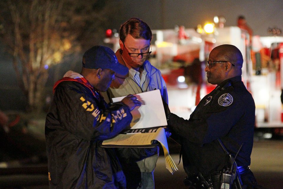 Photo -   Investigators review notes as fire fighters combat a fire in a west Jackson, Miss., home where authorities say a small plane carrying three people crashed shortly after 5 p.m. Tuesday evening, Nov. 13, 2012. The home's resident is believed to have escaped but authorities have not released names of plane's passengers. (AP Photo/Rogelio V. Solis)