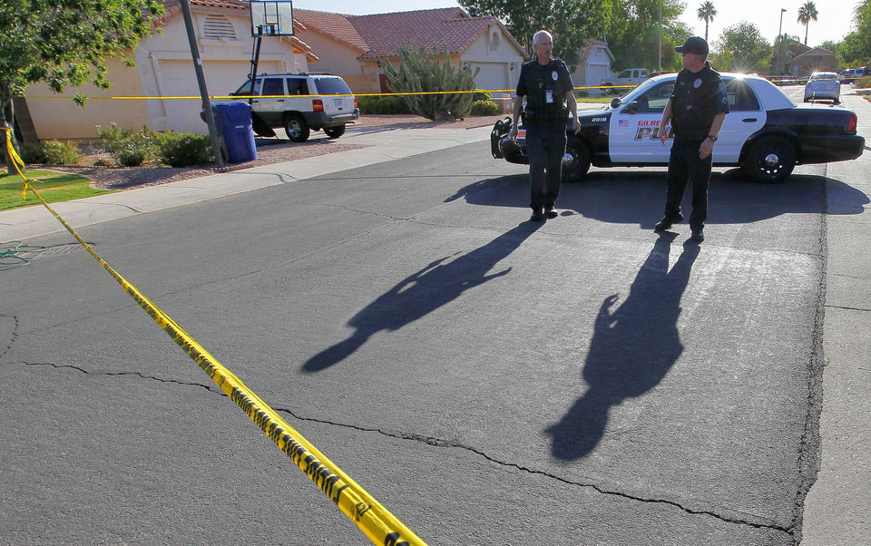 Gilbert police officers blocks the street outside a shooting crime scene Thursday, May 3, 2012 in Gilbert, Ariz. Gilbert police spokesman Sgt. Bill Balafas said Thursday that police believe Jason Todd Ready, 39, a former Marine with ties to neo-Nazi and Minutemen groups, shot four people Wednesday and then took his own life in a suburban Phoenix home. (AP Photo/Matt York)