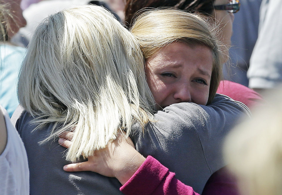 Photo - Freshman Hailee Siebert, 15, cries on her mothers shoulder after students arrived at a shopping center parking lot in Wood Village, Ore., after a shooting at Reynolds High School Tuesday, June 10, 2014, in nearby Troutdale. A gunman killed a student at the high school east of Portland Tuesday and the shooter is also dead, police said. (AP Photo/Rick Bowmer)