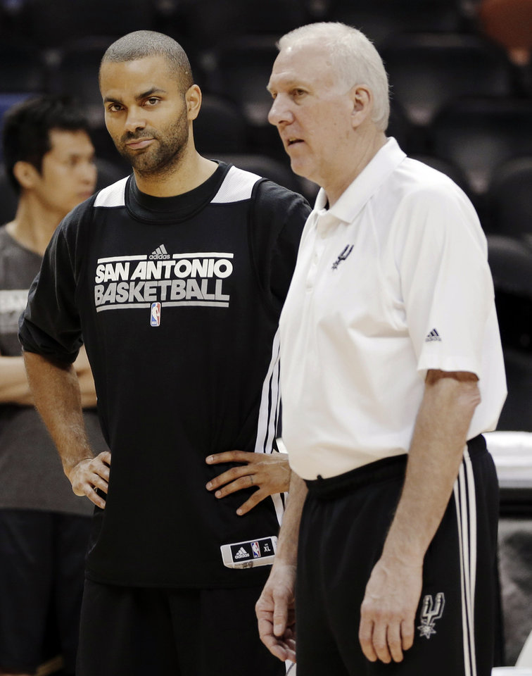 Photo - San Antonio Spurs' Tony Parker, left, and head coach Gregg Popovich talk during NBA basketball practice, Saturday, June 15, 2013, in San Antonio. The Spurs host the Miami Heat in Game 5 of the NBA Finals on Sunday, with the best-of-seven games series even at 2-2. (AP Photo/David J. Phillip)
