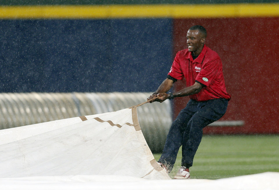 Photo - A member of the Atlanta Braves grounds crew works to cover the infield as rain begins to fall in the second inning of a baseball game against the Chicago Cubs, Saturday, May 10, 2014, in Atlanta. (AP Photo/John Bazemore)
