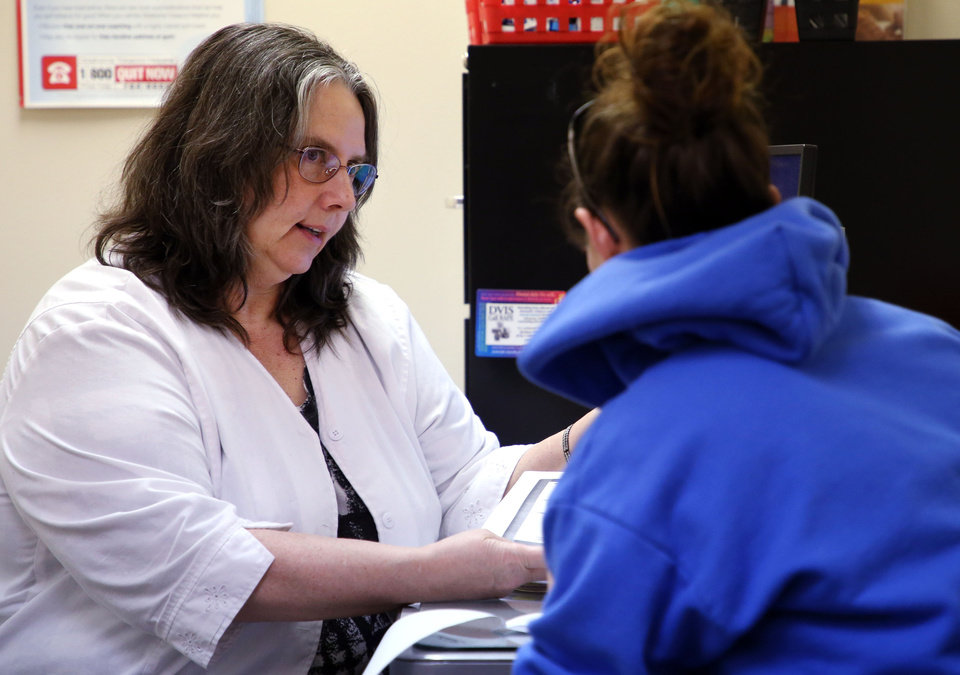 Photo - Debbie Caswell (left), a registered nurse at the Creek County Health Department, talks with a patient on Wednesday, Jan. 31, 2018. CORY YOUNG/Tulsa World