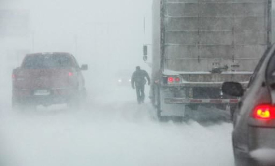 Photo -  Blizzard conditions in  Oklahoma City Thursday, Dec. 24, 2009. A driver walks to the front of his stuck semi on south  Oklahoma City. Photo by Jim Beckel,