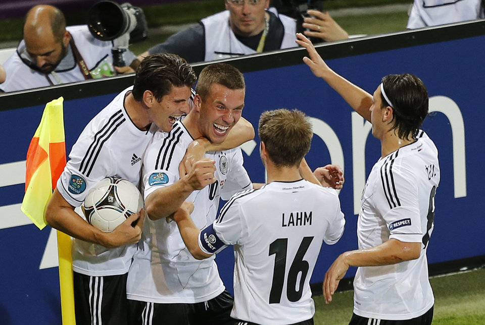 Germany's Lukas Podolski, second left, is celebrated by, from left, Mario Gomez, Philipp Lahm and Mesut Oezil after scoring the opening goal during the Euro 2012 soccer championship Group B match between Denmark and Germany in Lviv, Ukraine, Sunday, June 17, 2012. (AP Photo/Michael Probst)