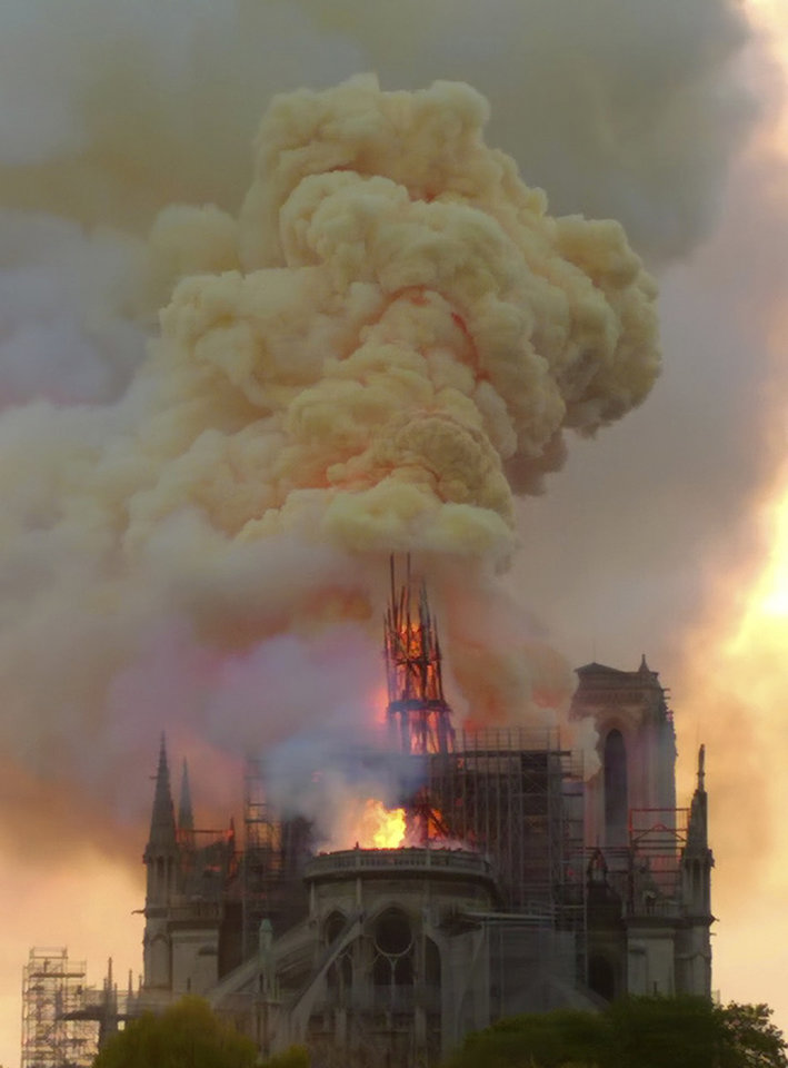 Photo - Flames and smoke rise as the spire of Notre Dame cathedral is on fire in Paris, Monday, April 15, 2019. A catastrophic fire engulfed the upper reaches of Paris' soaring Notre Dame Cathedral as it was undergoing renovations Monday, threatening one of the greatest architectural treasures of the Western world as tourists and Parisians looked on aghast from the streets below. (AP Photo/Dominique Bichon)