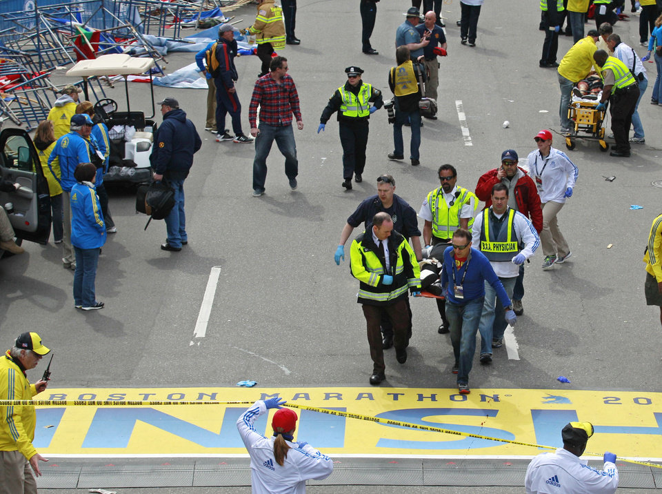 Medical workers wheel the injured across the finish line during the 2013 Boston Marathon following an explosion in Boston, Monday, April 15, 2013. Two explosions shattered the euphoria of the Boston Marathon finish line on Monday, sending authorities out on the course to carry off the injured while the stragglers were rerouted away from the smoking site of the blasts. (AP Photo/Charles Krupa) ORG XMIT: MACK121