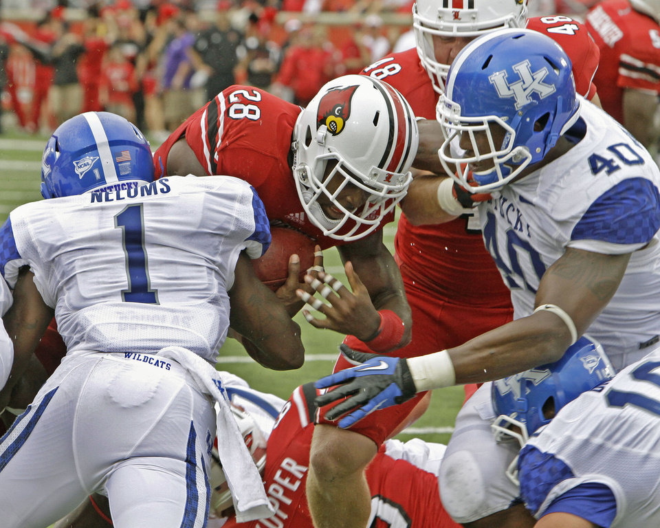 Photo -   Louisville running back Jeremy Wright (28) muscles through Kentucky defenders Martavius Neloms (1) and Avery Williamson (40) to score the first touchdown of the year during an NCAA college football game at Cardinal Stadium in Louisville, Ky., Sunday, Sept. 2, 2012. (AP Photo / Garry Jones)
