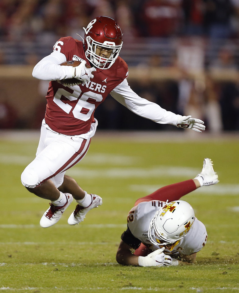Photo - Oklahoma's Kennedy Brooks (26) leaps past Iowa State's Greg Eisworth (12) during an NCAA football game between the University of Oklahoma Sooners (OU) and the Iowa State University Cyclones at Gaylord Family-Oklahoma Memorial Stadium in Norman, Okla., Saturday, Nov. 9, 2019. [Bryan Terry/The Oklahoman]