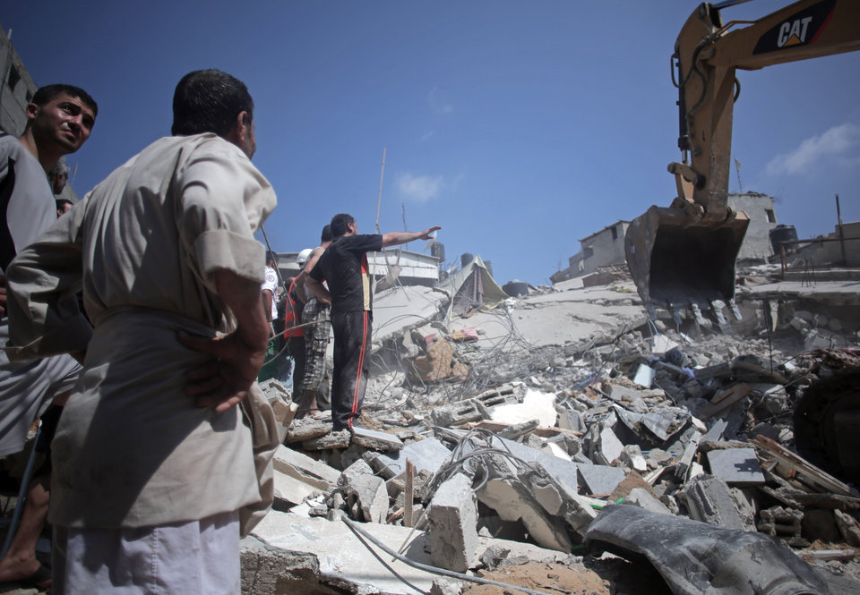 Photo - Palestinian rescuers search for bodies and survivors in the rubble of homes which were destroyed by an Israeli missile strike, in Gaza City, Monday, July 21, 2014. On Sunday, the first major ground battle in two weeks of Israel-Hamas fighting exacted a steep price, killing scores Palestinians and over a dozen Israeli soldiers and forcing thousands of terrified Palestinian civilians to flee their devastated Shijaiyah neighborhood, which Israel says is a major source for rocket fire against its civilians. (AP Photo/Khalil Hamra)