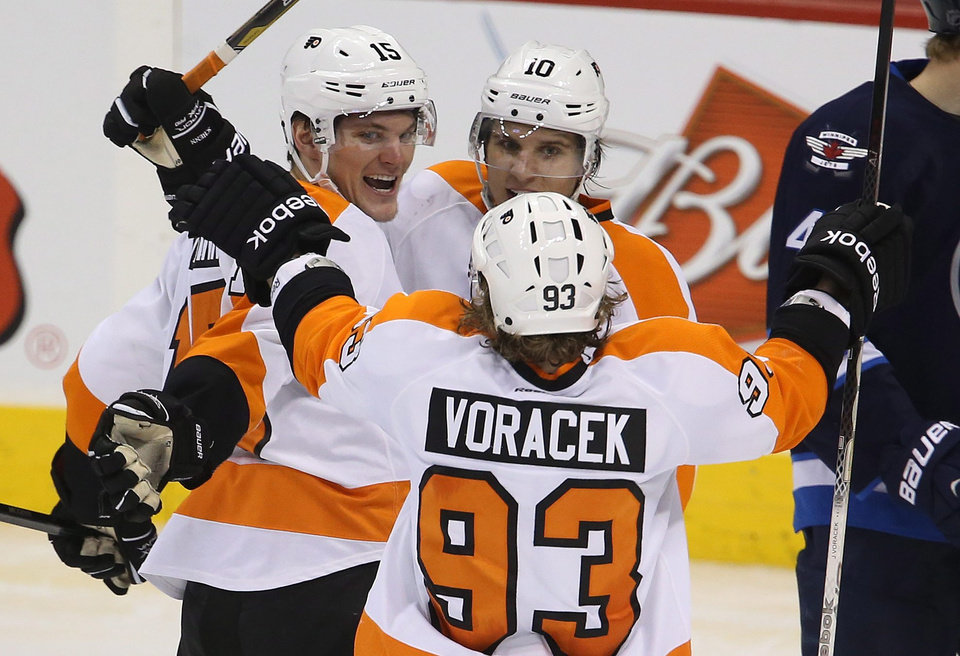 Philadelphia Flyers\' Tye McGinn (15) celebrates his goal against the Winnipeg Jets with teammates Brayden Schenn (10) and Jakub Voracek (93) during the third period of an NHL hockey game in Winnipeg, Manitoba, Tuesday, Feb. 12, 2013. (AP Photo/The Canadian Press, Trevor Hagan)