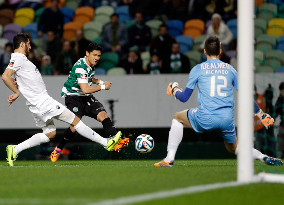 Photo - Sporting's Montero, from Colombia, center, attempts a shot at goal in front of Academica's goalkeeper Ricardo Nunes during their Portuguese league soccer match Sunday, Feb. 2 2014, at Sporting's Alvalade stadium in Lisbon. (AP Photo/Armando Franca)