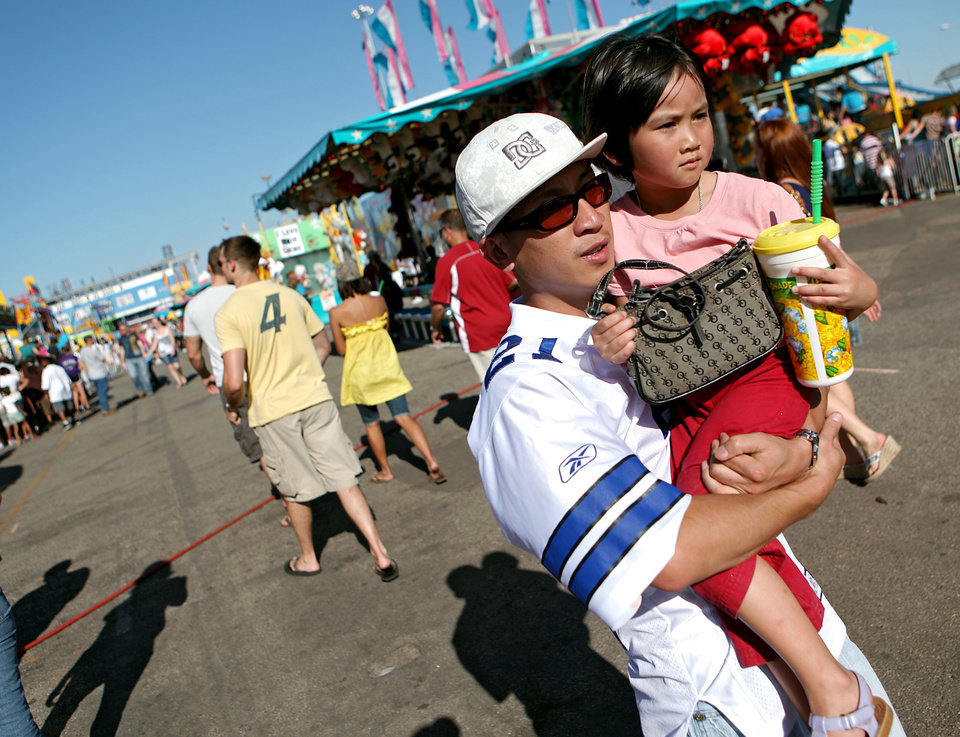 Photo - Jay Chan, of Oklahoma City, carries his niece Christine Somsack, age 4, through the midway at the 2009 Oklahoma State Fair at State Fair Park in Oklahoma City on Sunday, Sept. 27, 2009.  By John Clanton, The Oklahoman ORG XMIT: KOD