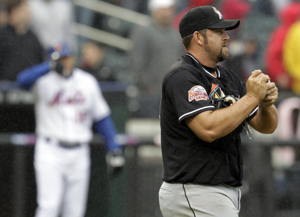 Miami Marlins relief pitcher Heath Bell wipes the the ball during the ninth inning of a baseball game against the New York Mets, Thursday, April 26, 2012, at Citi Field in New York. The Mets won 3-2. (AP Photo/Seth Wenig).