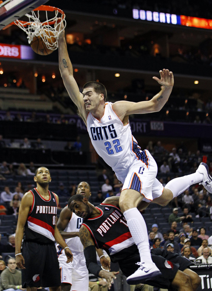 Charlotte Bobcats\' Byron Mullens (22) dunks over Portland Trail Blazers\' LaMarcus Aldridge (12) during the first half of an NBA basketball game in Charlotte, N.C., Monday, Dec. 3, 2012. (AP Photo/Chuck Burton)