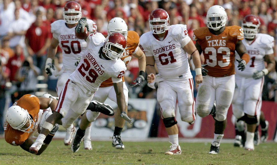 Photo - OU's Chris Brown runs past Keenan Robinson of Texas during the Red River Rivalry college football game between the University of Oklahoma Sooners (OU) and the University of Texas Longhorns (UT) at the Cotton Bowl in Dallas, Texas, Saturday, Oct. 17, 2009. Photo by Bryan Terry, The Oklahoman