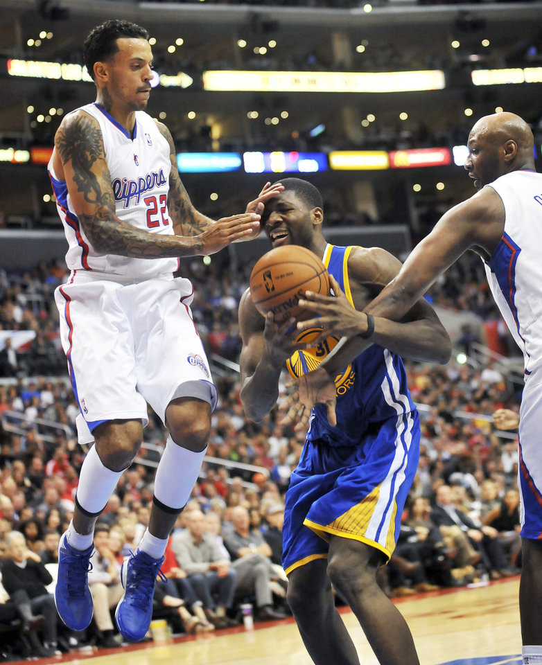 Photo -   Los Angeles Clippers forward Matt Barnes, left, and forward Lamar Odom, right, defend as Golden State Warriors center Festus Ezeli drives to the basket in the first half of an NBA basketball game in Los Angeles on Saturday, Nov. 3, 2012. (AP Photo/Richard Hartog) ,