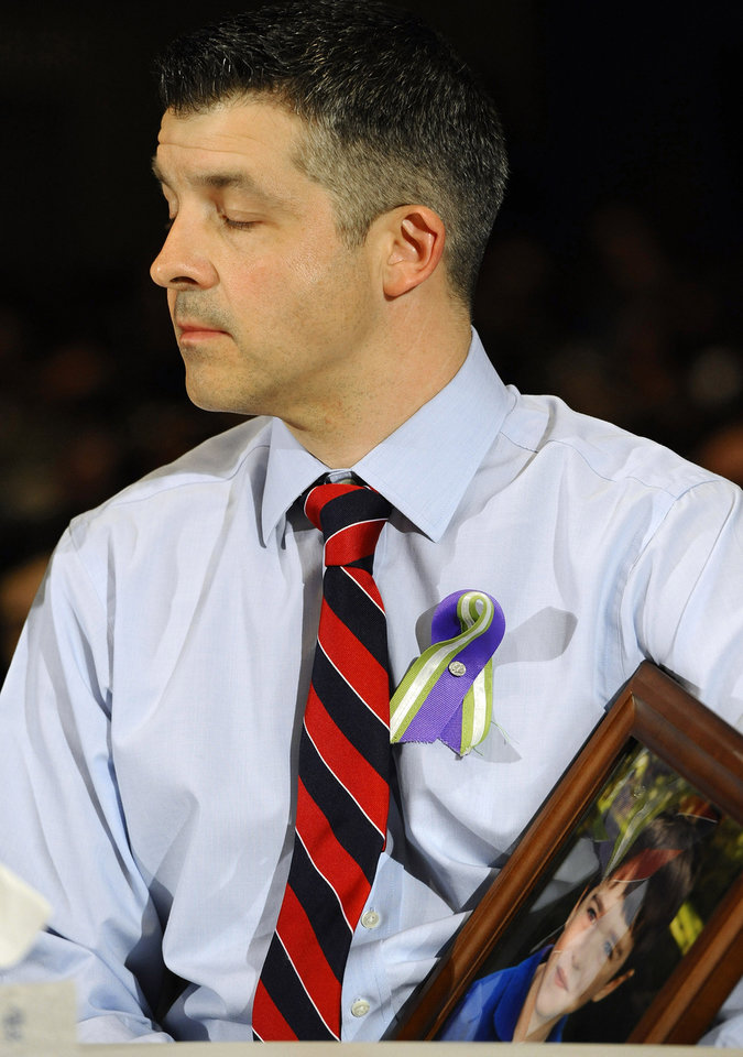 Photo - Ian Hockley, father of Sandy Hook School shooting victim Dylan, holds a photo of his son as he listens during a hearing of a legislative task force on gun violence and children's safety at Newtown High School in Newtown, Conn., Wednesday, Jan. 30, 2013. Connecticut lawmakers are in Newtown for the hearing, where those invited to give testimony include first responders and families with children enrolled at Sandy Hook Elementary. (AP Photo/Jessica Hill)
