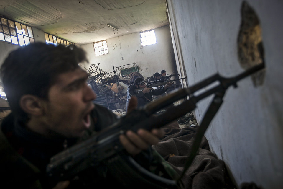 Photo - In this Saturday, Dec. 15, 2012 photo, Free Syrian Army fighters aim their weapons as they chant religious slogans during heavy clashes with government forces at a military academy besieged by the rebels north of Aleppo, Syria. Free Syrian Army fighters took control over the military academy after battling government forces for several hours. (AP Photo/Narciso Contreras)
