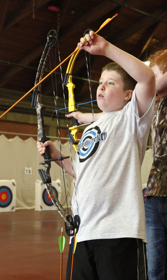 "Fifth-grader Will Jordan, age 10, from Sequoyah Elementary in Shawnee, selecting an arrow while participating in a regional ""Oklahoma Archery In The Schools"" shoot at State Fair Park in Oklahoma City Thursday, Feb. 14, 2013. Photo by Paul B. Southerland, The Oklahoman"